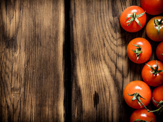 Fresh red tomatoes . On wooden background.