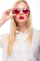 Beautiful blonde girl in pink glasses and shirt. Beauty face. Isolated on white background.