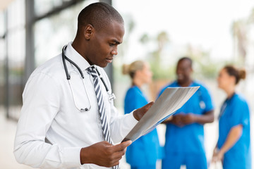 african medical worker looking at patient's x-ray