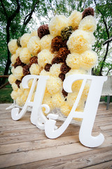 Flower pompon backdrop wall, wedding decoration zone with double letters a. Yellow white and brown color.