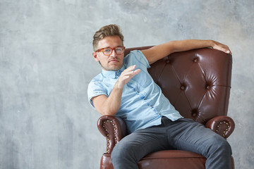 Portrait of a stylish intelligent man stares into the camera, small unshaven, charismatic, blue shirt, sitting on a brown leather chair, dialog, negotiation, short sleeve, brutal, hairstyle