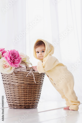 Cute Baby Girl Standing Near The Basket Of Flowers Stock Photo And