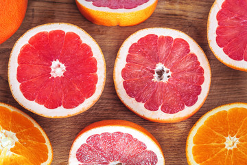 Fresh Grapefruits and Oranges sliced on wooden background