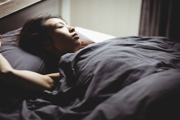 Brunette sleeping on the bed