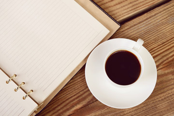 cup of coffee and organizer on a wooden table