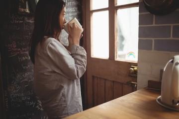 Brunette drinking coffee in front of the door