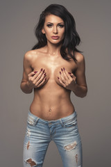 Sexy attractive brunette woman posing only in jeans in studio