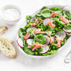 Smoked salmon, spinach, green pea and radish salad.  Delicious lunch. On a light background