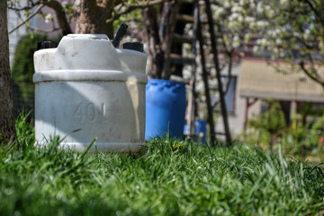 Water tank for watering the grass. Container to retain rainwater in the garden. White plastic jerrycan. Gallon water reserve