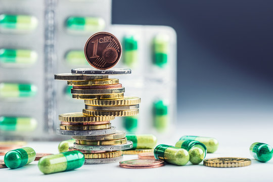 Euro money and medicaments. Eurocoins and pills. Coins stacked on each other in different positions and freely pills scattered around. Reimbursement of medicinal products in health care.