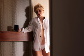 Frau mit Kaffeetasse steht in Tür