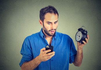 perplexed business man with alarm clock looking at smart phone