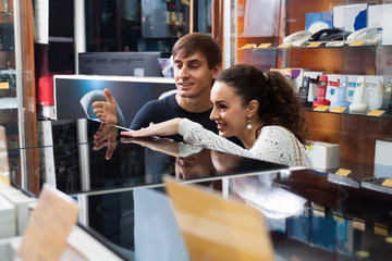 Young couple choosing kitchen stove