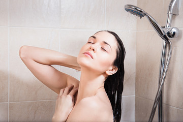 Young woman washing her head under the shower