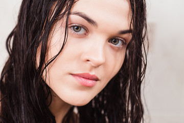 Portrait of a beautiful brunette with wet hair in the shower