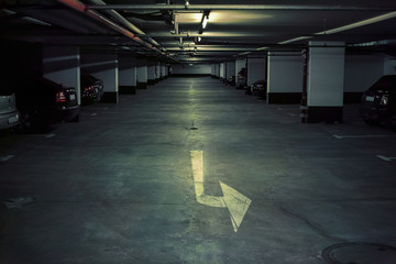 Car parking.Dark, low light underground garage with cars and marking arrows on the floor.