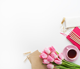 Tulips, keyboard and office supplies on white board