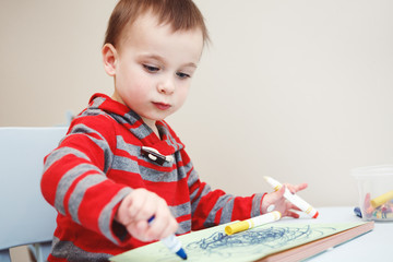 Portrait of cute Caucasian white little boy toddler drawing with color pencils markers on paper in album, looking serious, engaged in process