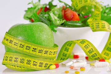 Diet concept - green apples, lettuce, pills and  measure tape