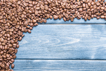 Coffee seeds on blue wood background.