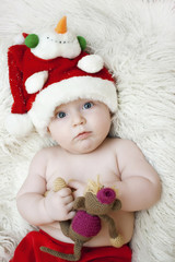 The baby in a red Christmas hat with a toy in the hands of