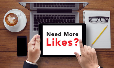 Need More Likes? message on tablet pc screen held by businessman