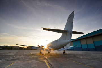 Small aeroplane infront of aircraft hangar during sunrise