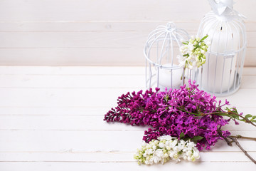 Fresh white and violet lilac flowers and candles on white painte