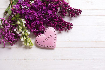 Fresh white and violet lilac flowers and decorative pink heart