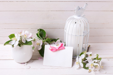 Apple blossom, candle in decorative bird cage and empty tag on w