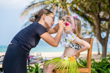 Young woman makes the child's face painting. Fancy dress party on the beach.