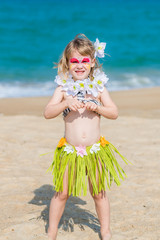 Smiling little girl with  face painting in Hawaiian costume on the beach. Fancy dress party.