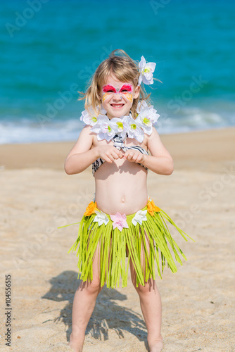 1bd925c01f76 Smiling little girl with face painting in Hawaiian costume on the beach. Fancy  dress party.