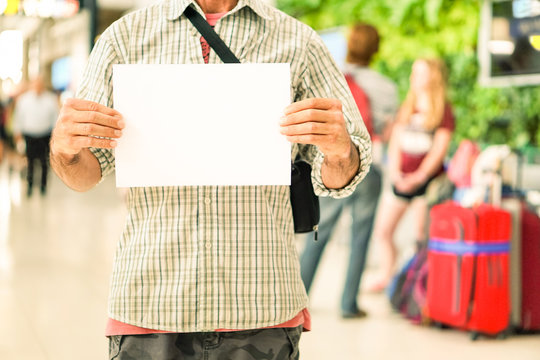 Man hands holding empty signboard at international airport meeting point - Young casual guy with blank sign for advertising text is receiving travelers at arrival  gate -