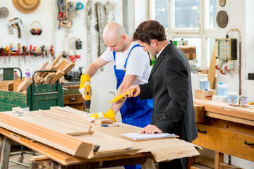 boss and worker in carpenter's workshop