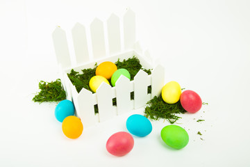 Colorful dyed eggs for Easter in a basket on white background