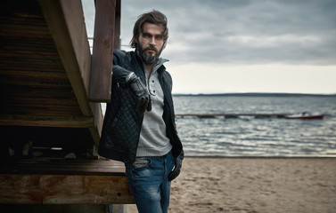 Portrait of a mature handsome guy resting on the autumn beach - fototapety na wymiar