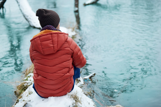 Man on solo camping trip. Winter gear walking along fast flowing rocky river, in scenic outdoor nature destination