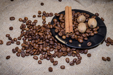 Plate and coffee beans, nutmegs  and cinnamon sticks on a sack background