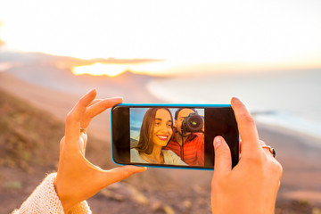 Female hands making selfie photo with smart phone on the beautiful island landscape background. Close-up view photo on the screen