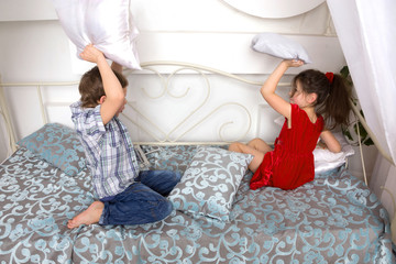 Boy and girl fighting pillows and playing on the bed.
