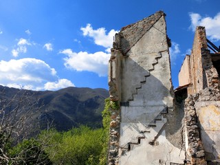 Abandoned crumbling building showing stairs in Italian village of Balestrino - Landscape color photo