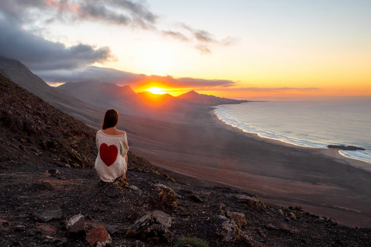 Young woman enjoying beautiful sunset sitting on the mountain with great view on Cofete coastline on Fuerteventura island