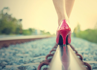 Female legs in red high heels on the rail of the railway. (Vinta