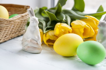 Easter decoration with yellow tulips, ceramic rabbits and colored eggs over light background