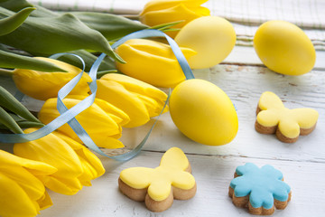 Easter eggs, homemade cookies and yellow tulips over light background with copy space