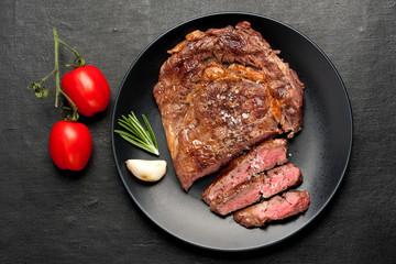 Wall Mural - Medium rare grilled Steak Ribeye on dark background. Top view