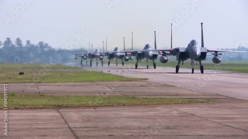 Numerous F-15 and F-16 fighter jets line up and taxi for