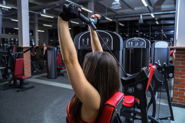 Athletic young woman work out with nautilus equipment in the gym