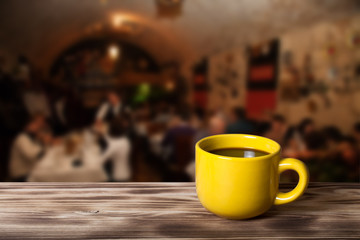 Coffee in cup on wooden table opposite a blurred background